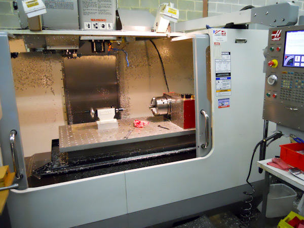 The two knuckles are produced on a Haas VFS computer-numeric control milling machine with a fourth axis.