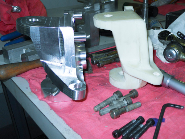 A finished aluminum steering knuckle sits next to its prototype, created in the college's lab facilities using fuse definition modeling with ABS extruded plastic.