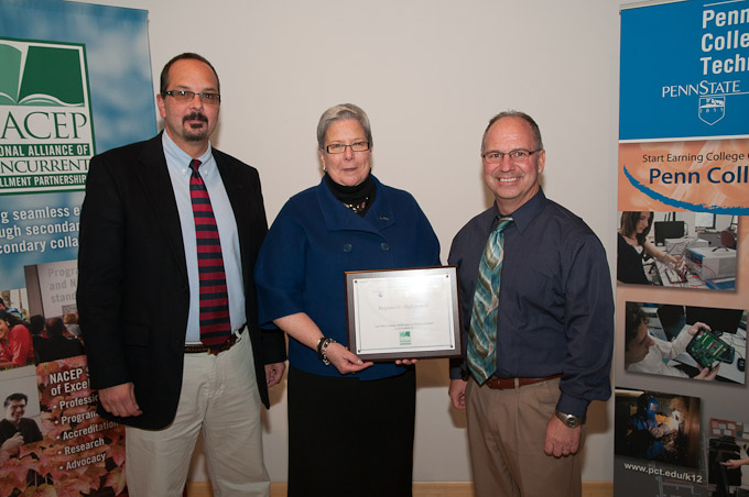 Pennsylvania College of Technology President Davie Jane Gilmour presents a plaque to Hughesville High School administrators James Bower, left, career coordinator, and Ron Lorson, right, principal, in honor of the school's participation in the college's dual-enrollment program.