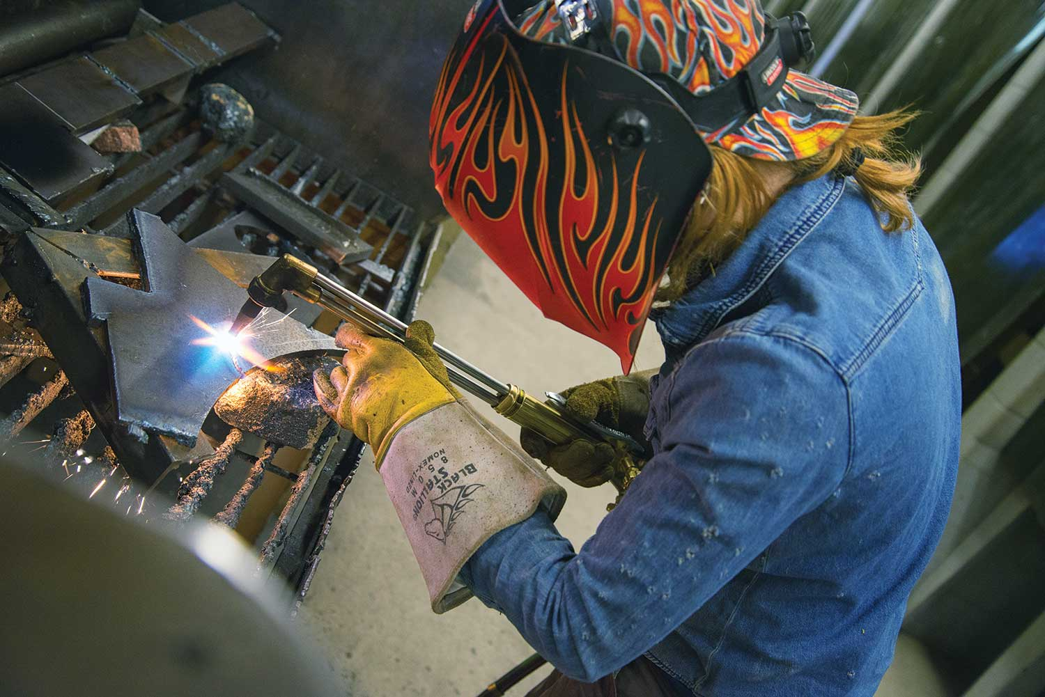 Using the tools of the welding lab – an oxy-acetylene cutting torch - Hannah Michelle cuts a steel plate.