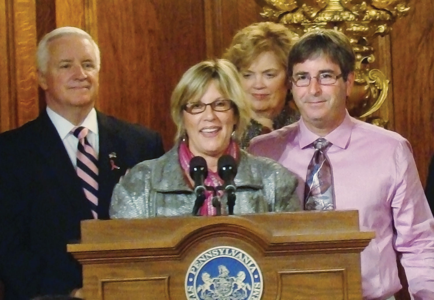 Backed by her husband, Greg, right, and former Gov. Tom Corbett, Spinello speaks at the signing of the Pennsylvania Breast Density Notification Act. Photo courtesy of the Pennsylvania Breast Cancer Coalition.