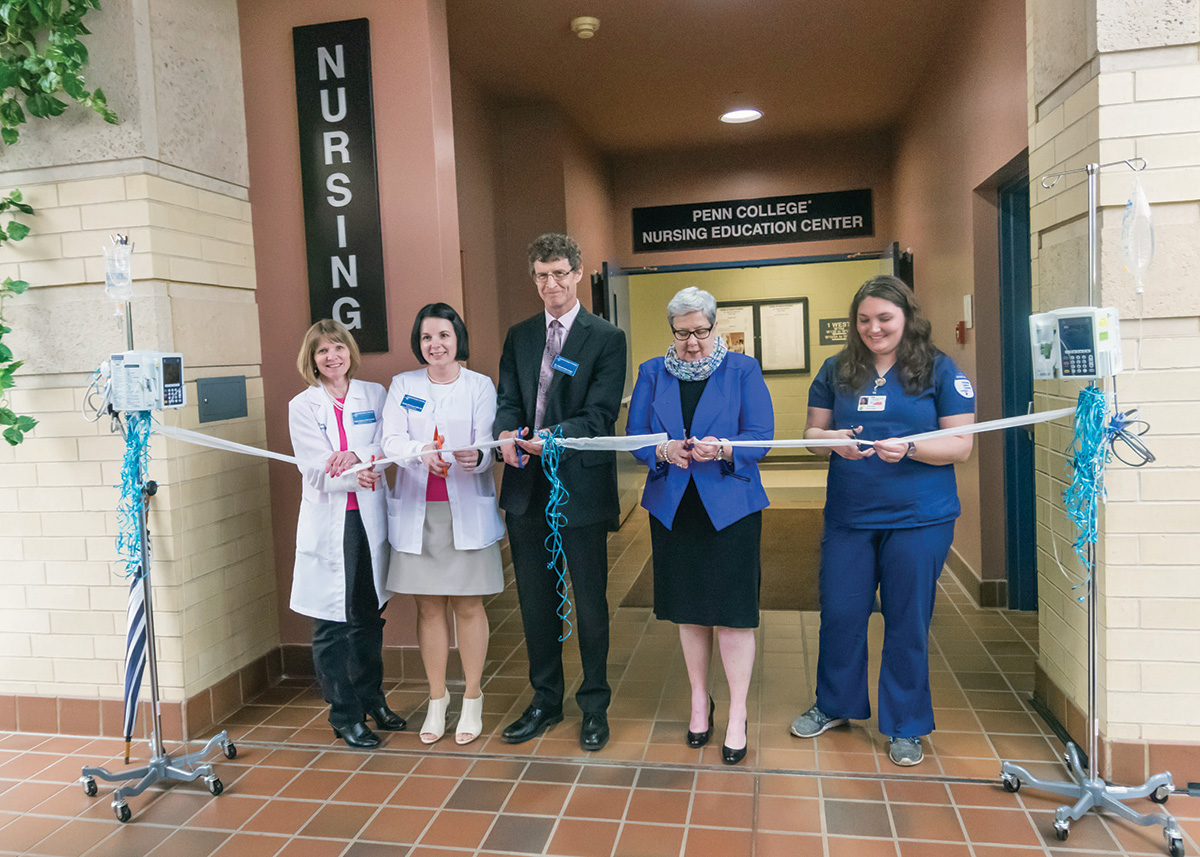 "Cutting the ""ribbon"" (gauze held by IV poles) are, from left, Dottie M. Mathers, associate professor of medical-surgical nursing; Sandra L. Richmond, director of nursing; Edward A. Henninger, dean of health sciences; President Davie Jane Gilmour; and student Monica A. Flexer, president of the Penn College Student Nurses Association. Photo by Tia G. La"