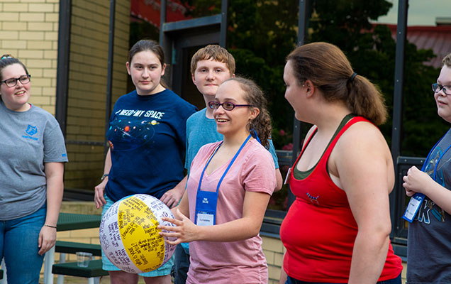 Girl holding beach ball during icebreaker activity
