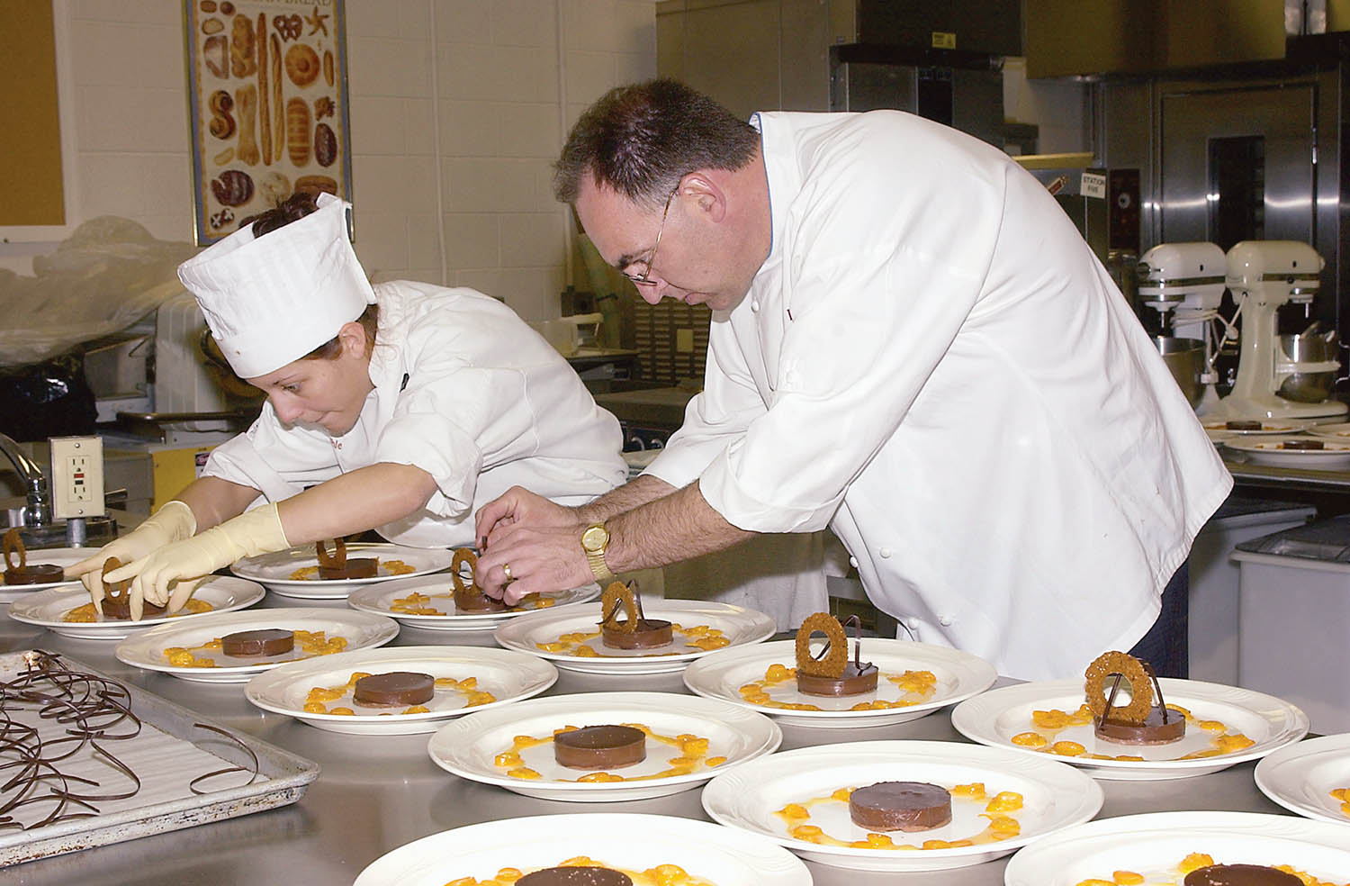 In 2003, a student works alongside Chef David Robins, then-executive pastry chef for the Corner Café and Buckhead Bread Co. Photo by Cindy Davis Meixel.