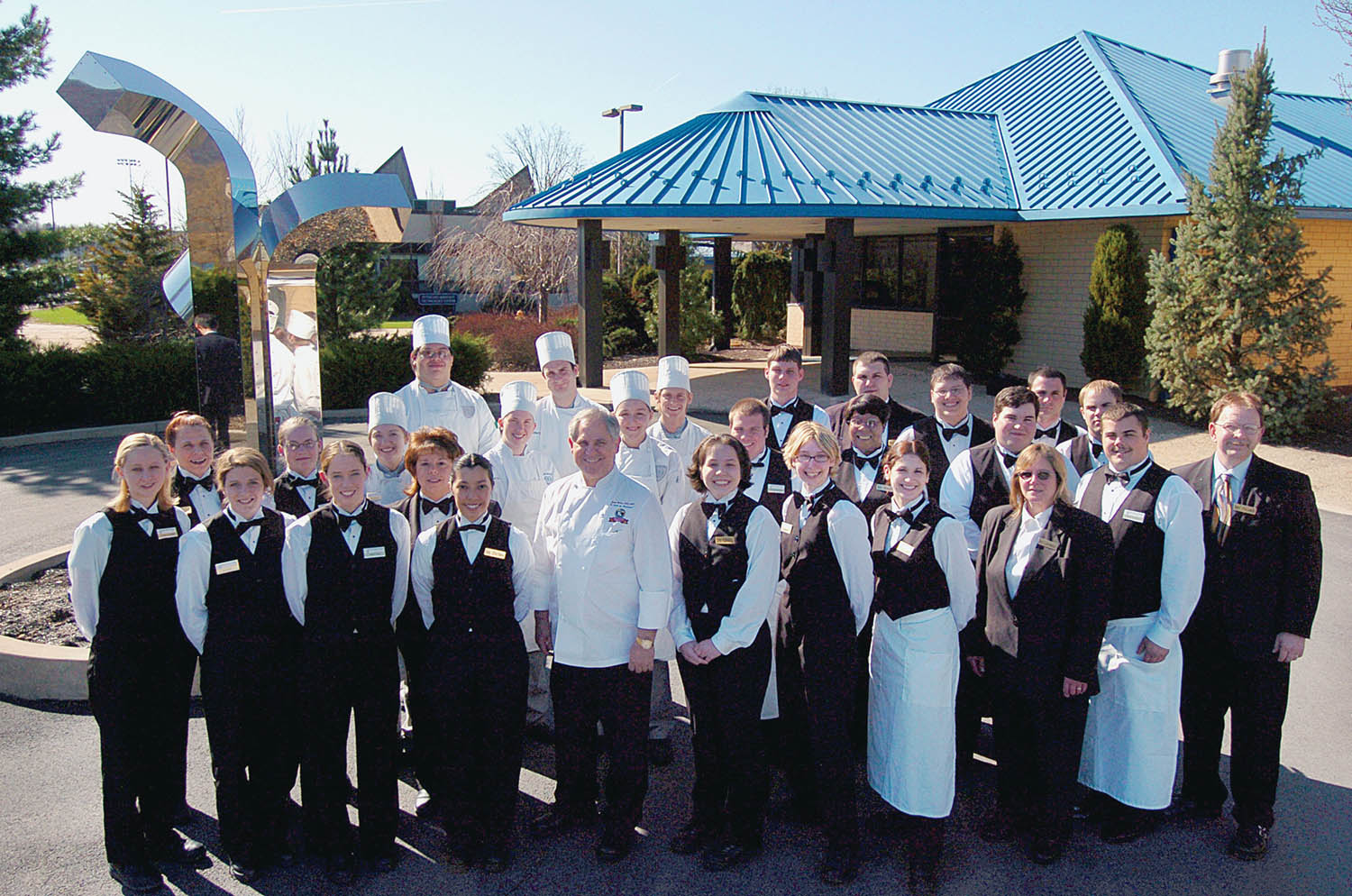 During his sixth visit in 2005, Chef John Folse gathers with students and staff outside Le Jeune Chef Restaurant. Photo by Jennifer A. Cline.