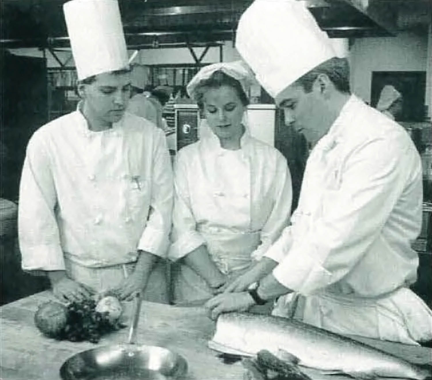 During preparation for the college's first Visiting Chef dinner in 1992, students Ric Newton and Vanessa Buck study the technique of Visiting Chef Richard L. Kimble Jr. Photo by Cindy Davis Meixel.