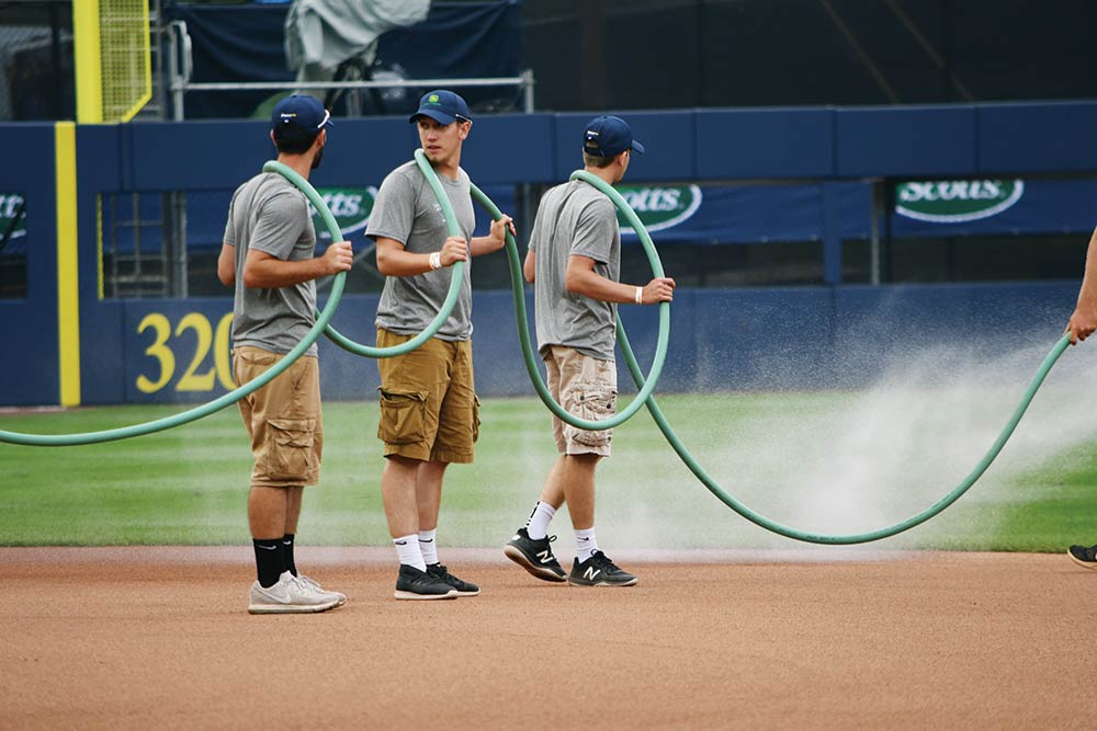 Wildcats lend a hand as the grounds crew waters the infield to keep dust down. From left: Remington Spoonhour, Barnyak and Devon Sanders.