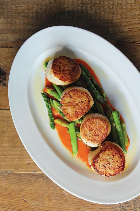 Among her spring dinner menu dishes are seared sea scallops with asparagus, preserved lemon and roasted red pepper.