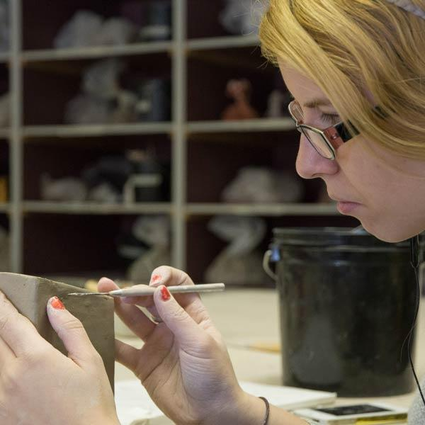 Student working on pottery project