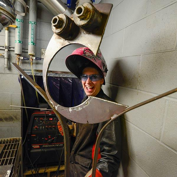 Student framed in welding sculpture