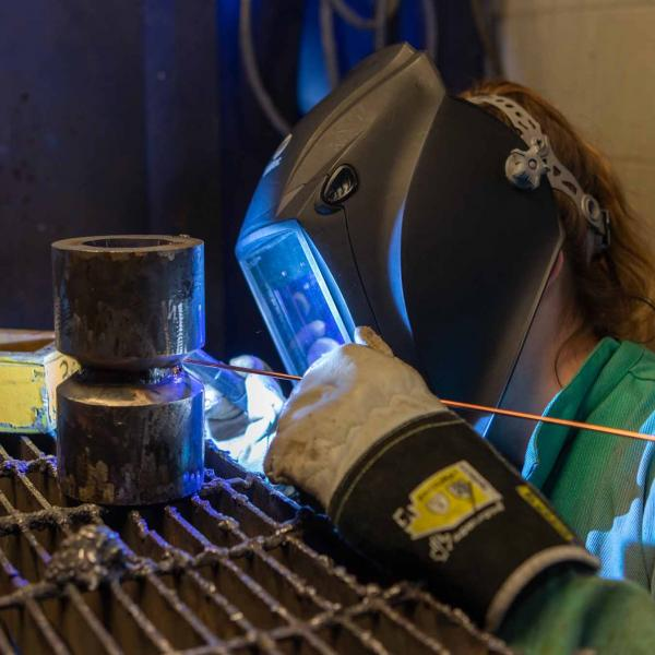 Student welding in lab